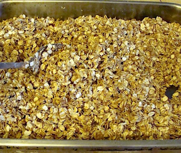 Stirring homemade granola in baking pan