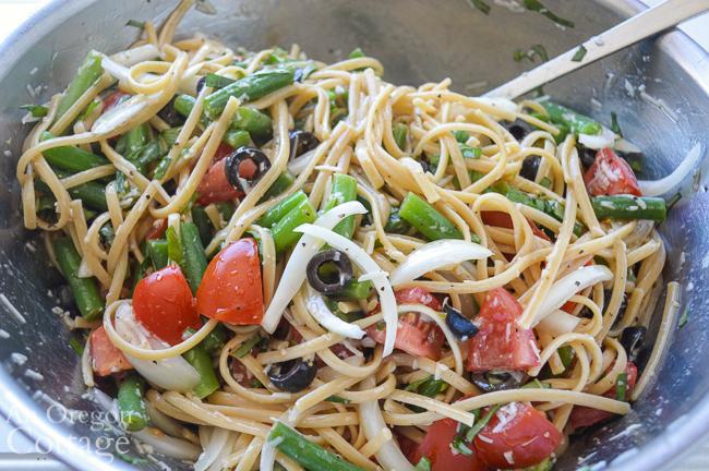 tossing summer pasta salad