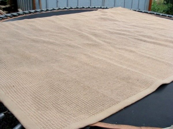 Cleaned jute rug on trampoline