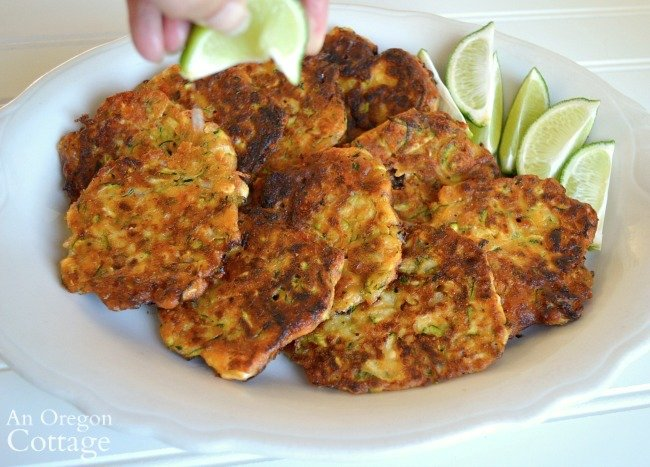 squeezing lime on zucchini feta fritters