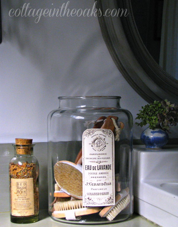 Vintage apothecary jars in cottage bathroom