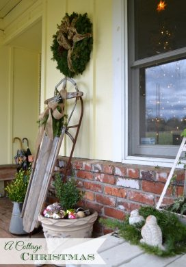 A Cottage Christmas Porch with vintage sled and greenery