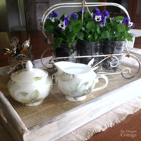 Pint Mason jars and live pansies in a vintage glass holder on tea tray