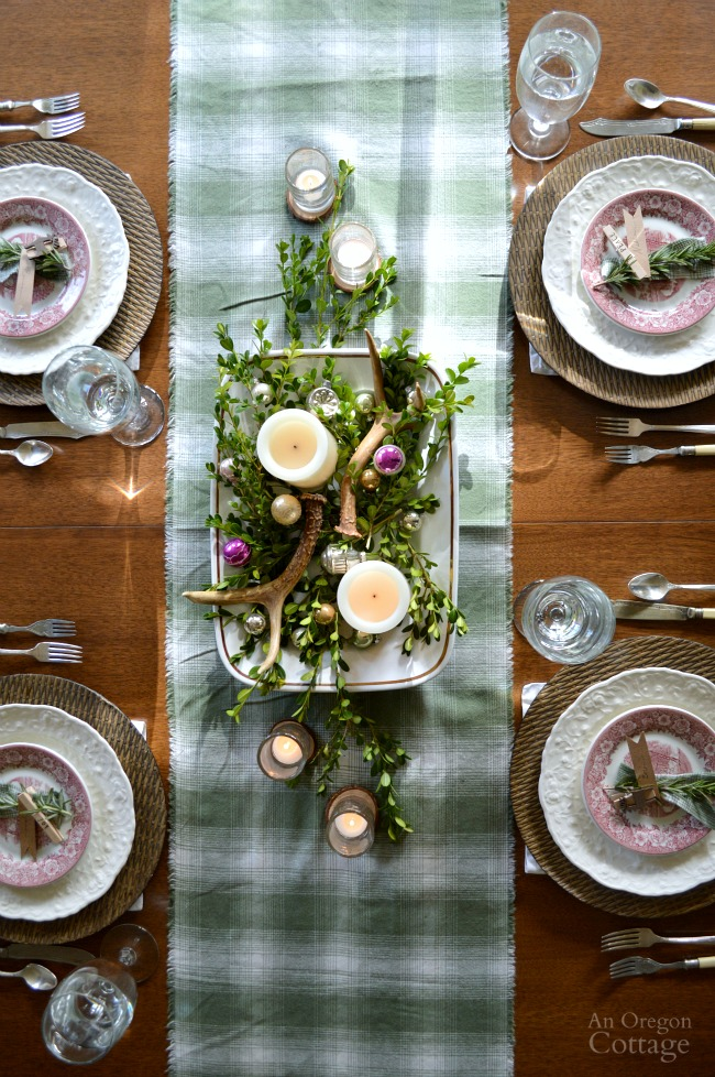 Green Plaid-Rustic Christmas Table set with simple greenery, candles, antlers, and wood slices.