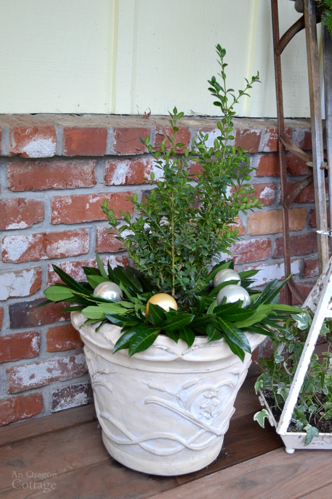 Christmas Porch simple planter with boxwood, laurel leaves and ornaments