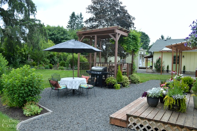 Garden backyard with gazebo, gravel patio, and planting beds.