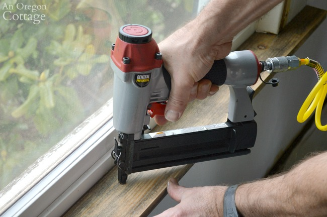 Using a nail gun on sill of 1920s farmhouse window trim DIY