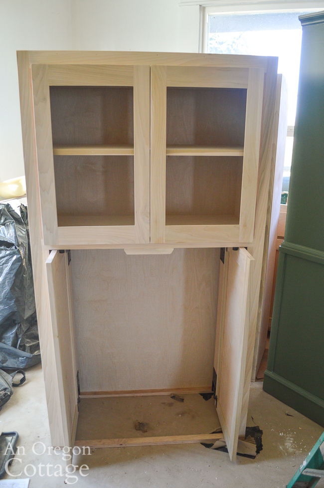 custom coffee bar cabinet with pocket doors on bottom and glass doors on top.