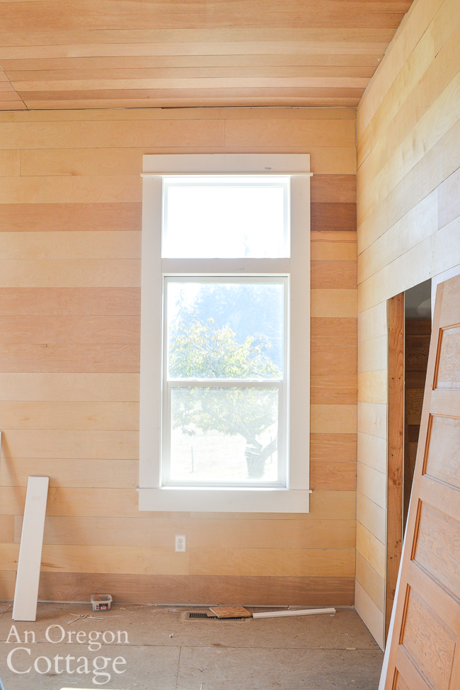 farmhouse master bed unpainted wood walls and window