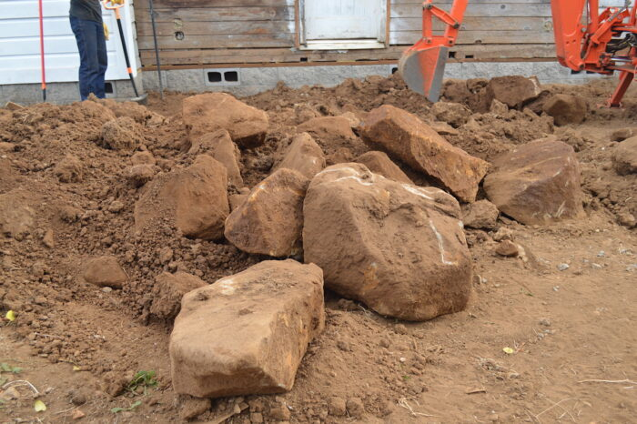 excavating boulders from side of farmhouse