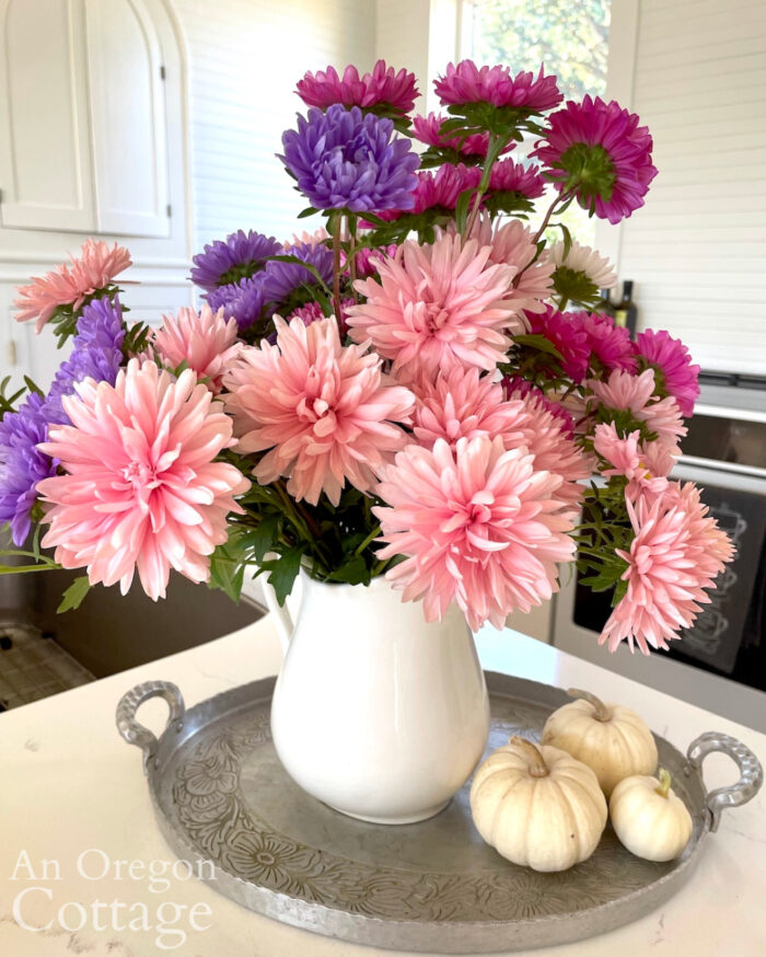 autumn giant aster bouquet in white pitcher